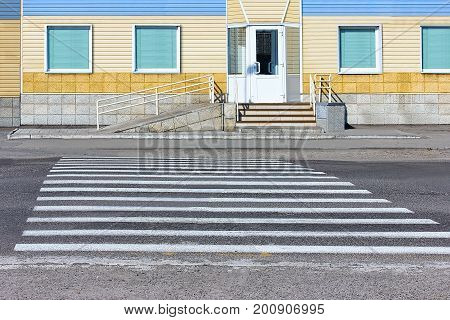 Building, facade with a siding finish, road, pedestrian crossing, staircase, handrail.