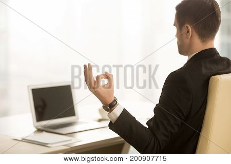 Close up of hand in chin mudra yogic gesture, mindful calm yogi businessman meditating at workplace near laptop, doing yoga exercise, practicing breathing, meditation at work, no stress, back view
