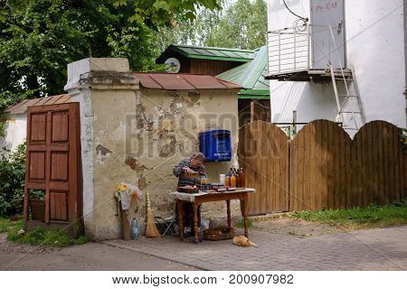 SUZDAL/ RUSSIA - AUGUST 19, 2017. An elderly russian woman selling bottles of Mead, jars with jam and ups of berries in the historical center of Suzdal, Vladimir region, Russia.