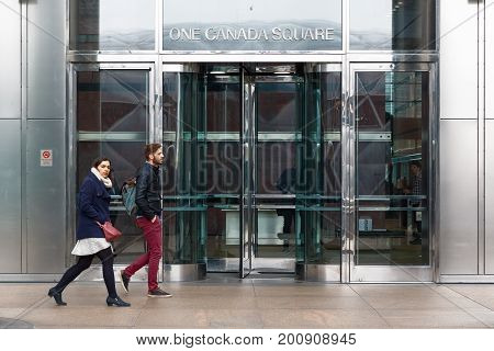 London UK - May 24 2017 - Entrance of One Canada Square a skyscraper in Canary Wharf with people walking in motion in front of the doors
