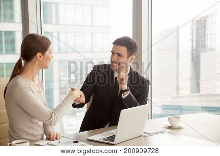 Smiling businesswoman and businessman handshaking, introduction and getting acquainted, making good impression at first meeting, welcoming new hire employee, shaking hands as greeting gesture