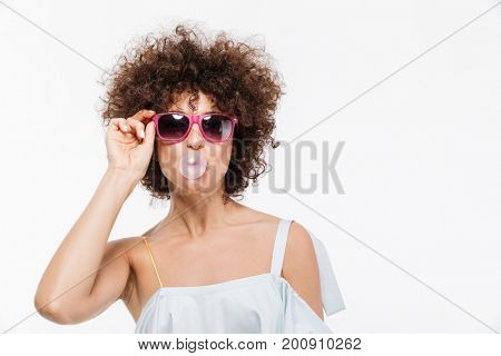 Positive young woman in sunglasses blowing bubbles while chewing a gum isolated over white background