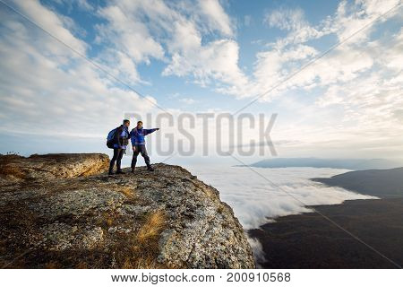 Two climbers standing on top of summit above clouds in the mountains. Man pointing with his hand discussing route. Plan, vision and mission concept.