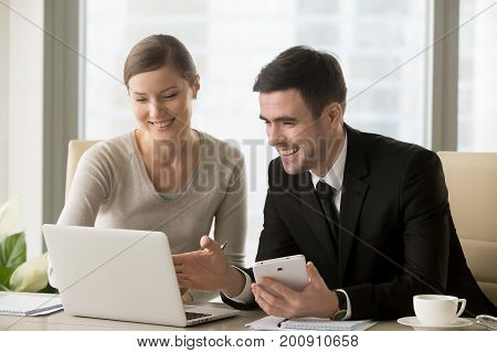 Smiling happy businessman and businesswoman sitting at workplace, using laptop and digital tablet, smart devices for easy business management, enterprise software and apps, integrated tech solutions
