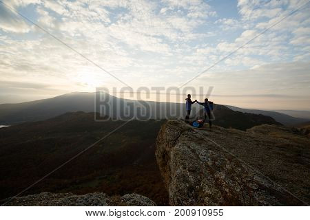 Two climbers standing on summit above clouds in the mountains holding hands. Silhouettes of hikers celebrating ascent on sunset. Cooperation, synergy, friendship concept. poster
