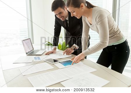 Smiling professional designers working on project at office desk, creating design for client concept, using color pantone swatches and construction plans of residential houses and commercial property