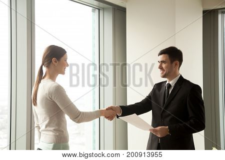 Happy businessman and businesswoman shaking hands while standing in office, satisfied partners reach agreement after effective successful negotiations, making sealing good deal, concluding contract