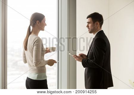 Smiling business team members talking during coffee break, young businessman and businesswoman having pleasant conversation in office, good friendly human relations of colleagues, love affair at work
