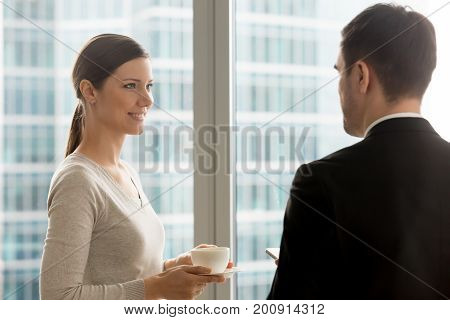 Attractive businesswoman listening to businessman talking at coffee break, happy lady holding cup and having informal conversation in office, smiling woman looking at colleague during discussion