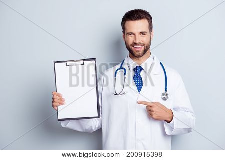 Cheerful Handsome Bearded Smiling Intern Is Holding The Clipboard. Doc Is Wearing White Uniform And