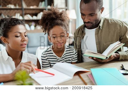 Mom And Dad Helping Daughter With Homework
