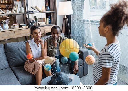 Girl Telling Parents About Solar System