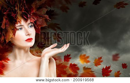 Autumn Woman Showing Empty Copy Space on the Open Hand against Cloudy Sky. Beautiful Fashion Model with Fall Leaves Fantasy Autumn Season Concept