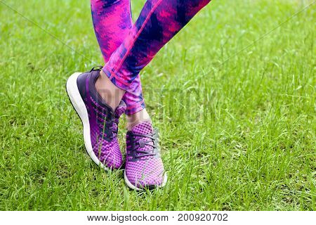 Female legs in leggings and purple sneakers on green grass