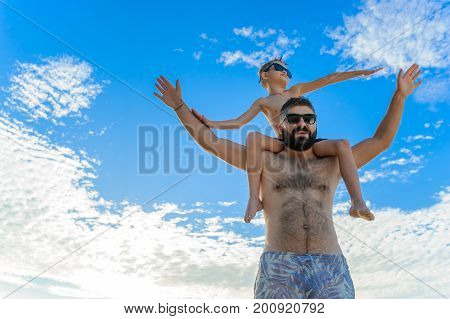 Eight years old boy sitting on dad's shoulders. Both in swimming shorts and sunglasses having fun on the beach. Bottom view. Blue sky and altocumulus clouds behind them