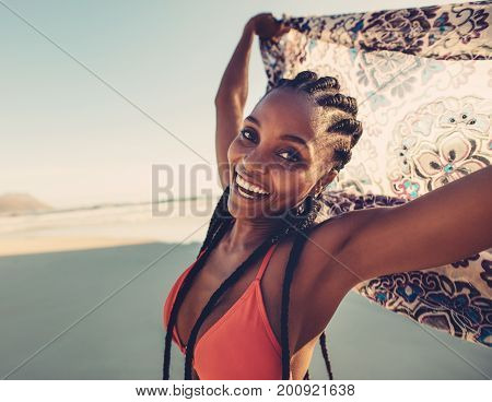 African woman in bikini on the beach holding scarf in the air. Young female with scarf looking at camera.