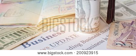 Money and passport with on letter book Business News update Concept of graduate education MBA abroad in university requires a lot foreign currency Dollars to bring success in famous institution