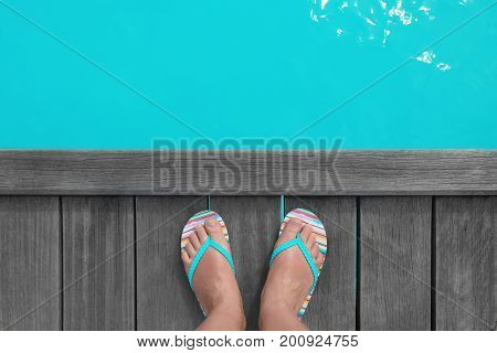 Feet of woman in flip-flops standing on wooden pontoon at sea resort. Summer vacation concept