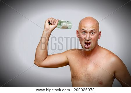 A drunkard drinks from a bottle. bald man