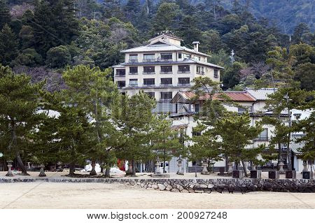 Modern multi-storey building on Miyajima island  among coniferous forests near the city of Hatsukaichi in Hiroshima Prefecture in Japan.