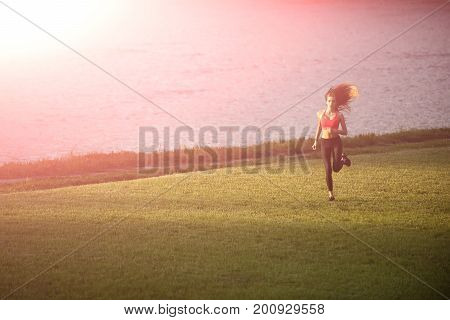 Runner and success. Girl sunny outdoor. Sport and sportswear fashion. Woman running on green grass. Coach or trainer at workout.