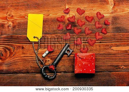 set of little red valentine hearts near present package and metallic key with yellow label or tag on brown vintage wooden background top view