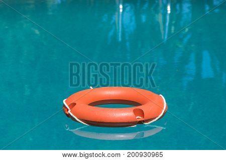 Orange lifebuoy on blue swimming pool water surface