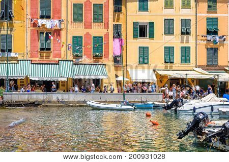 PORTOFINO, ITALY - JUNE 26, 2017: Daylight beautiful view to Portofino, Italy buildings with people walking and shopping on sidewalk. Ships on water.