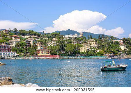 SANTA MARGHERITA LIGURE, ITALY - JUNE 27, 2017: Beautiful view to city, beachline and ship cruising on water. Santa Margherita Ligure resort, Italy
