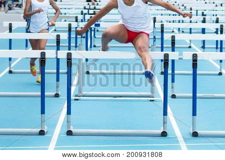 High school girls racing in the 100 meter hurdles on a blue track at a track and field competitioin.