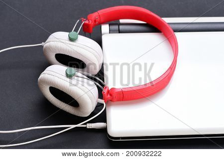Earphones Made Of Plastic With Computer. Headphones And Silver Laptop