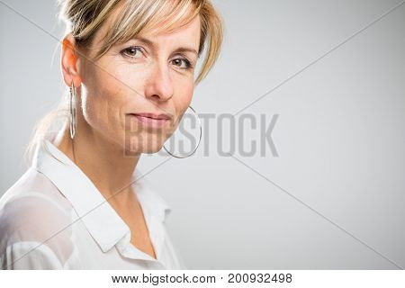 Portrait of a smiling middle aged caucasian woman against light grey background - radiating confidence and feminity (shallow DOF; color toned image)