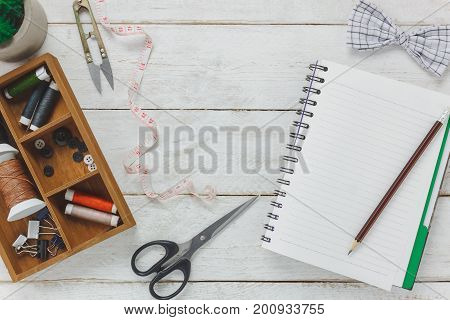 Top view accessories tailor concept.Tailor tools is cutting scissors bow tie spools of thread buttons and sewing clothes. Notebook for free space text on rustic wooden background.