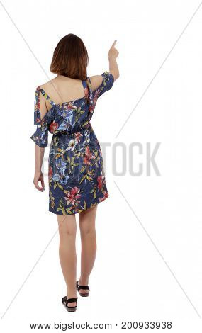 Back view of  pointing woman in dress. beautiful girl. Rear view people collection.  backside view of person.  Isolated over white background. Girl in dress in flower shows thumb up