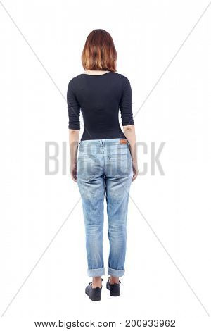 back view of standing young beautiful  woman.  girl  watching. Rear view people collection.  backside view of person. A girl in jeans and a black T-shirt is standing with her back