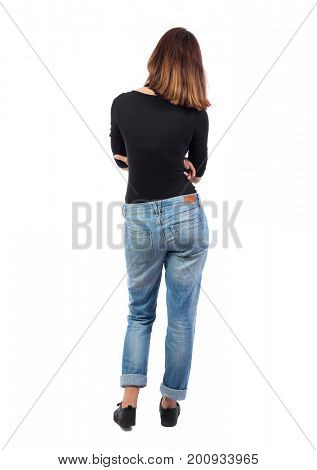 back view of standing young beautiful  woman.  girl  watching. Rear view people collection.  backside view of person. A girl in jeans and a black T-shirt is looking thoughtfully and looking up