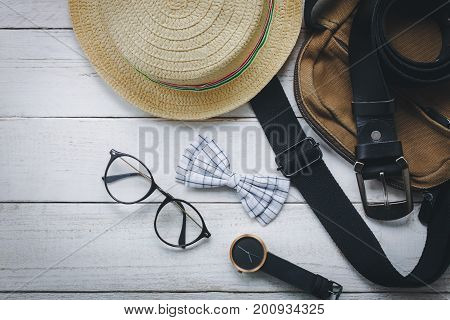 Top view of accessories to travel with fashion man clothing concept. Several essential items for gentlemen or teenage and adult.Mix of variety object on modern rustic white wooden office desk.