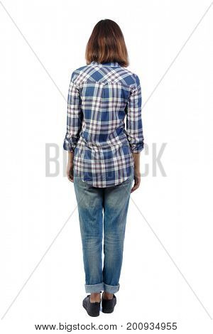 back view of standing young beautiful  woman.  girl  watching. Rear view people collection.  backside view of person. A girl in a plaid shirt is standing and looking into the distance.