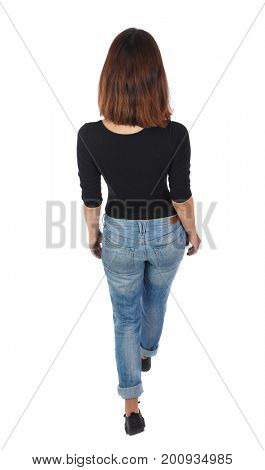 back view of walking  woman. beautiful blonde girl in motion.  backside view of person.  Rear view people collection. The top view of the girl in jeans and a black T-shirt goes into the distance.