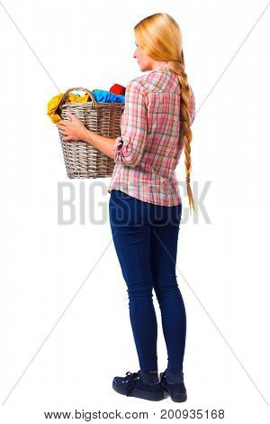 Back view of woman with  basket of dirty laundry. girl is engaged in washing. backside view of person.  Isolated over white background. Girl with very long hair holds up a laundry basket.