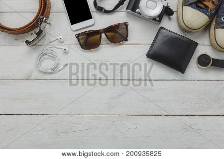 Flat lay of accessory to travel on holidays concept.Outfits for teens and young traveler. Variety mix object on modern white table wood background. Essential items for travelling. Empty space to text