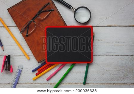 Top view back to school concept and business office supply background concept.backboard with stationery office beautiful color pencil staple eyeglasses notebook and magnify on wooden table.Copy space