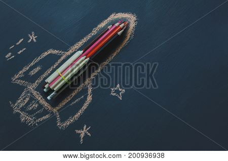 Top view rocket fling on the space with star.Crated by colorful pencil and drawing by chalk board on backboard or table.Start up business.Back to school and education concept.flat lay.copy space.