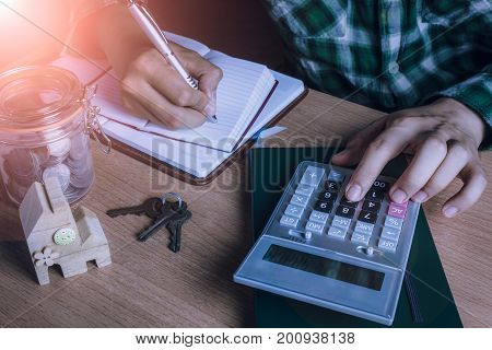 Asian man accountant or banker calculate finances / savings money or economy for rent home / house or condominium.Idea for save coin.Essential accessories on table office desk.Sun flare light.