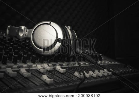 Headphones or Earphone on sound music mixer at home studio recording. Accessories idea for DJ or musician night club background.Black and white.Low key tone with copy space.