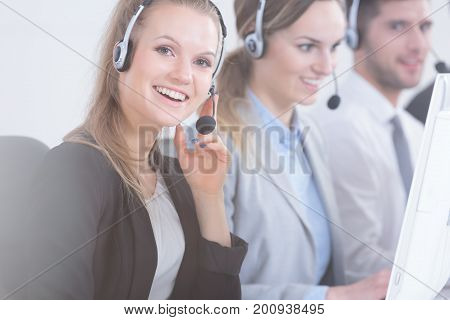 Young professional telemarketers wearing headsets and working