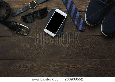 Overhead view of accessory men fashion with technology concept.Several items on the modern brown office desk background.Essential clothing for man business for working day and copy space.