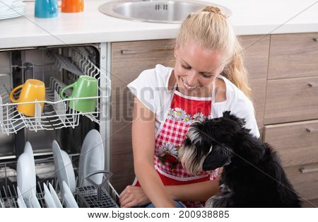 Pretty blonde girl sitting beside dishwashing machine and cute dog helping her with chores