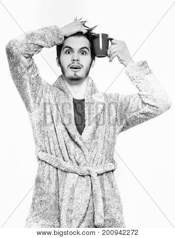 handsome surprised man or bearded sexy guy in blue terry bathrobe or dressing gown holds coffee or tea cup isolated on white background