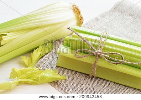 bunch of stalks of fresh green celery on flax material background